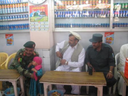 An ANA brigade commander, the governor of Khost, and the Khost police chief with a young girl in a downtown Khost ice cream shop.